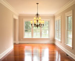 An unfurnished room in a home. There is a chandelier and three big windows.