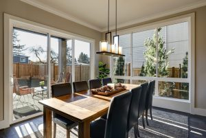 A sun-filled dining room in new luxury home boasts a rustic wood dining table with leather chairs surrounded by sliding glass doors that lead out to the patio.